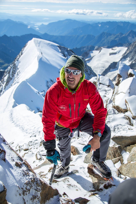 Kenton Cool in red jacket climbing up a mountain