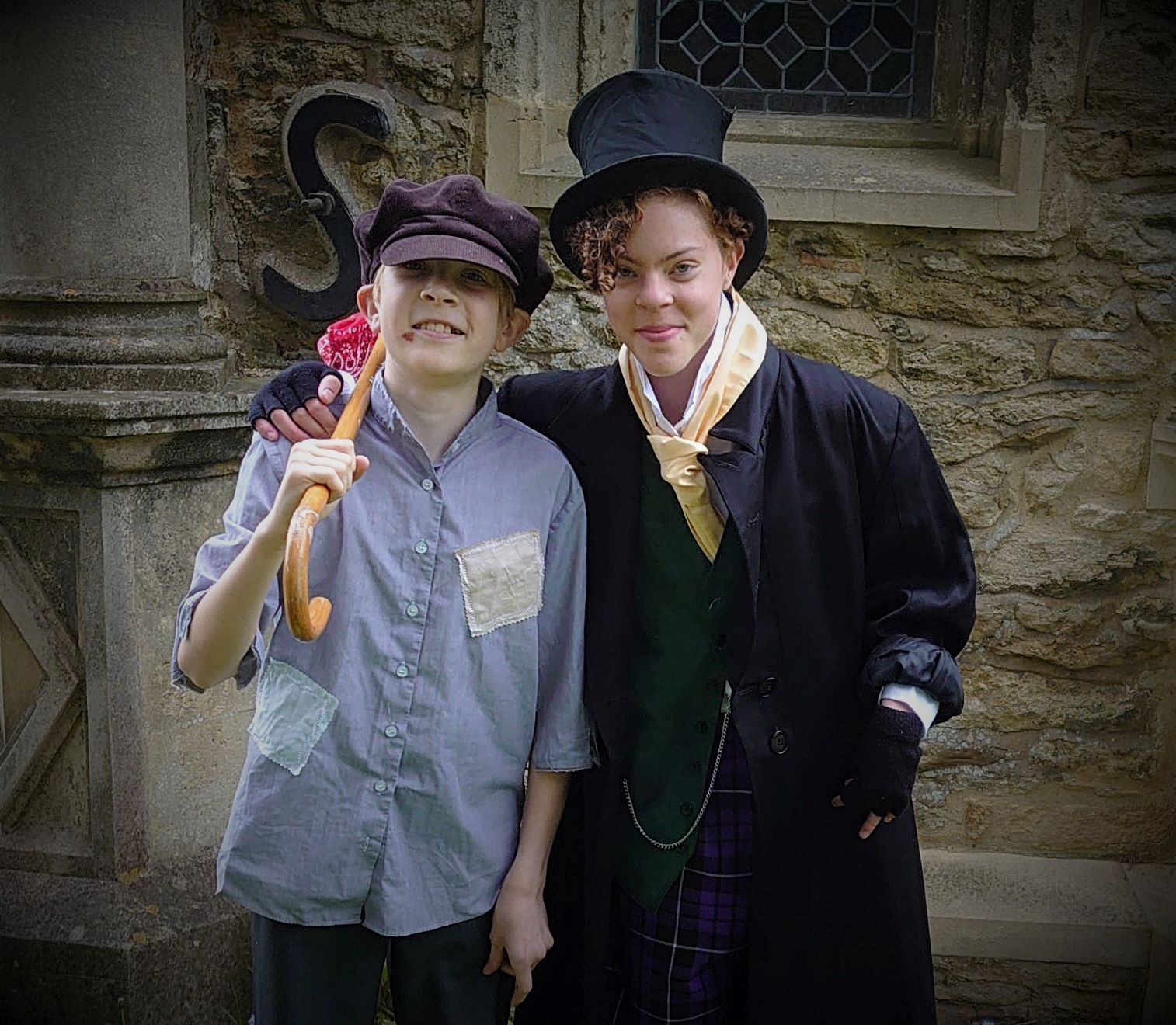 The Artful Dodger with his arm round Oliver's shoulders in front of a stone wall.