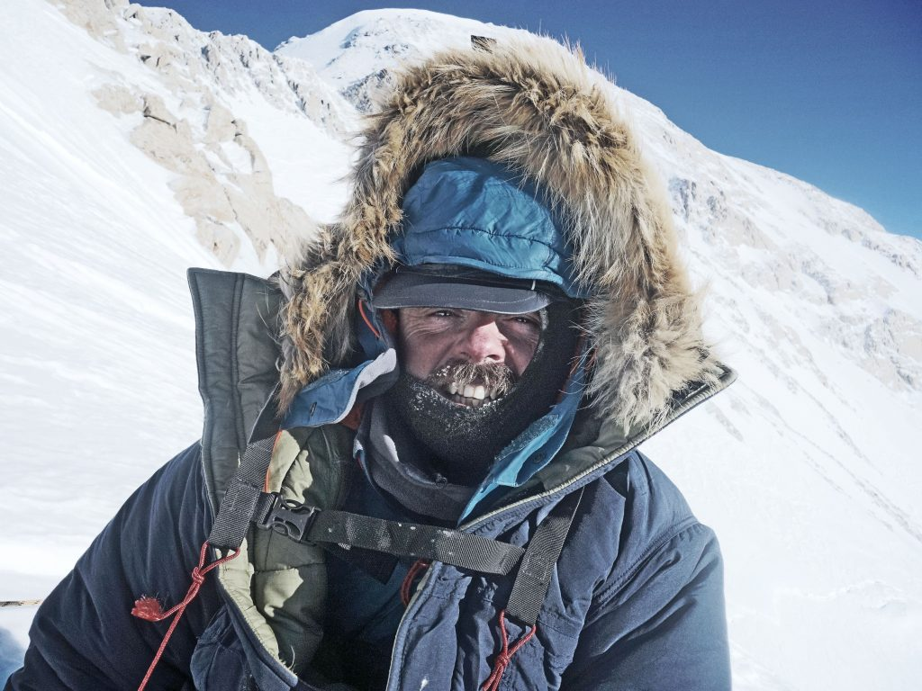 Kirkpatrick in a fur-lined hood with a snowy mountain background